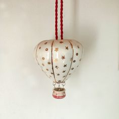 Holiday Hot Air Balloon ceramic from Chelonia Ceramics. 10% is donated to our current charity partner on Roots and Revival! A miniature porcelain hot air balloon, handcrafted with care to add wonder and whimsy to your space.