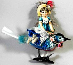 A fanciful Victorian girl sits atop a beautiful unsilvered clip-on bird from the early 1900s with a circa 1920s old-stock spun-glass tail and early vintage blue feather. The flowers on the girl's hat are salvaged from a 1890s bridal wreath. Hand signed by Gail Giaimo.