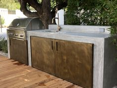 Modern wood patio with concrete outdoor kitchen and metal cabinet doors. Cooking space includes a built-in barbecue grill, a sink with brass faucet, refrigerator and storage cabinets. #patio #outdoorkitchen #outdoorcooking #outdoorcookingspace #outdoorliving #dreambackyard #outdoorkitchendesign #landscapearchitecture #landscapedesign  #california #californialiving #customkitchen #grill #barbecue #builtingrill #cookingoutdoors #metaldoors #cortensteel #concrete #brass #outdoorliving…