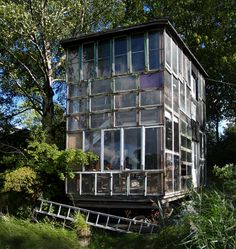 Glass house made from recycled glass windows in Freetown Christiania, neighborhood/commune in Copenhagen, Denmark created during the hippie movement.