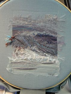 Machine and hand embroidery of a tidal surge, using glass sequins, metallic floss, satin, shredded organza and tulle on a Belgian linen.