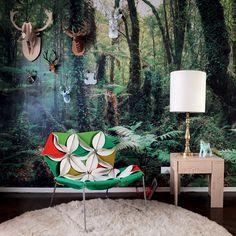 """Natureza na parede Ao entrar no apartamento decorado pelo arquiteto Maurício Arruda, a sensação é de ingressar em uma floresta. O efeito é causado pelo painel fotográfico da marca alemã Komar, que reveste a sala de estar e o corredor que leva aos quartos. A estampa chamativa foi solução para as dimensões do espaço: são apenas 3 metros de largura. """"Por conta do fundo escuro, ele aumenta a sensação de profundidade"""", revela o profissional."""