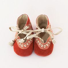 Handmade leather baby shoes made from coral pink suede leather. Embellished with a pink wavy leather trim and beige leather braiding. Fully lined in beige leather. Soft coral pink suede leather soles. Tasseled beige leather self-ties at ankle.