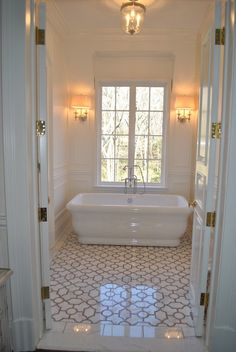 A Neutral White And Gray Bathroom Featuring Deep Ceramic Bathtub Patterned Tile Floors