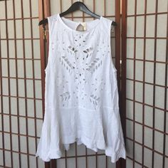 Free People Laser Cutout Tunic White tunic with cutout detailing. Absolutely adorable. Worn twice as a beach cover up. Tunic length. Hits at mid to upper thigh. Has keyhole cutout on back. Drop waist seam. It's so sweet. The perfect addition to a summer wardrobe. Excellent condition minus the wrinkles from storage! Free People Tops Tunics