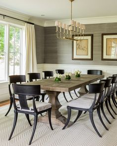 Transitional dining room features upper walls clad in gray grasscloth and lower walls clad in wainscoting alongside a Restoration Hardware Dumont Rectangular Dining Table atop a natural herringbone rug lined with Klismos Classic Side Chairs illuminated by Table Design, Dining Room Design, Dining Room Sets, Dining Room Chairs, Dining Room Furniture, Side Chairs, Black Dining Chairs, Office Chairs, Dining Area