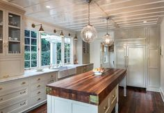 Love this farmhouse kitchen especially the light fixtures and warm tone that the floor and butcher block island bring.