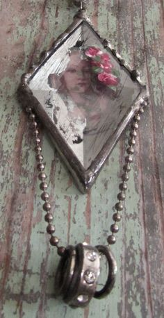 A pretty vintage reproduction print was put under a beveled piece of glass that looks like old worn mirror, soldered and then hand painted with some roses.    Hangs with silk ribbon, embellished with dainty ball chain and some metal rings.    Glass measures approx. 3 x 2 Overall pendant measures approx. 5    One of a kind      Carefully packed - Priority Mail - Insurance Upon Request