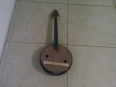 A sort of four string ukelele with banjo body and finger board, along with cardboard face and wood bridge