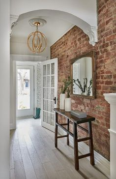 brick flooring A gold sphere pendant accented with a white medallion lights a long foyer hallway boasting a sawhorse console table placed on a gray wash oak floor beneath a reclaimed wooden mirror hung from an exposed brick wall. Brick Accent Walls, Faux Brick Walls, White Brick Walls, Exposed Brick Walls, Living Room Ideas Exposed Brick, Exposed Brick Apartment, Exposed Brick Kitchen, White Bricks, Painted Brick Walls