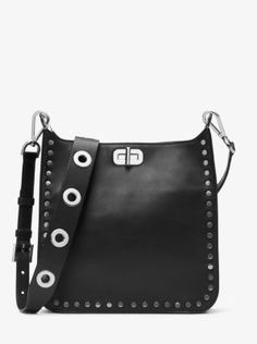 Crafted from ultra-smooth leather and embellished with flat studs, the Sullivan messenger offers an elevated way to accessorize. The sleek silhouette fastens with a turn-lock closure, while the grommeted guitar-inspired leather strap lends a downtown sensibility.