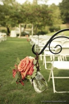 lining the aisle with shepherds hooks and floral arrangements in mason jars