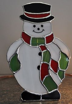 Snowman he is so cute, rollie pollie with his hat,scarf and mittens. He is 7 1/2 inches high and 4 1/2 inches wide and he has wire attached in the back so he can stand. He is made of white,red,green swirl glass and black opal glass for his shoes.His face and buttons are painted on. A great Christmas table decoration combine it with the Santa and Christmas tree light a great holiday decoration for your table.