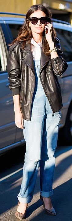 Black moto jacket worn over denim cuffed overalls and white top with snakeskin heels