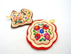 Here we have an incredible set of two vintage pincushions chock full of folk art goodness. Both are made from light almond-colored felt that has
