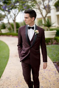 Orange county outdoor wedding shoot at monarch beach resort groom burgundy tuxedo with matching vest and white dress shirt with black bow tie and white floral boutonniere walking with hands in pockets