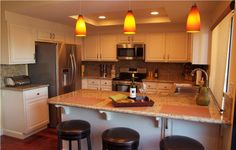 After ...Keeping the existing cabinets, this new kitchen is warm and inviting!  We removed the dated fluorescent lighting, extended the peni...
