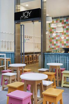 Interior Design for a Cupcake Shop with pink, orange and white table in front shop