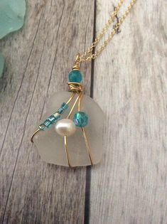 Beautiful white piece of sea glass wrapped in gold wire. Gorgeous blue glass beads and a freshwater pearl adorn this one of a kind piece. Perfect for a beach vacation or wedding