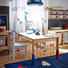 Un dormitorio infantil con una mesa de pino de altura regulable, sillas blancas y un mueble de pino con cajas de plástico