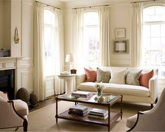 White and creamy white rooms have always been a favorite of mine. Living Room has a soft warm inviting feeling and the taupe and peachy pillows and accents give it character.