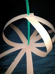 """* Kids Thanksgiving Crafts - Pumpkins -- Need: strips of orange paper (maybe 10 per pumpkin?), hole punch [pref. 1/4"""" hole, not standard hole], green pipe cleaner, green paper """"leaf""""  [maybe start by affixing a button to the bottom, so pipe cleaner won't pull through the bottom holes of the paper strips]"""