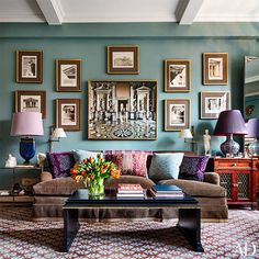 In the family room, a wall painted a Farrow & Ball blue hosts images of architectural elements, framed by J.Pocker, and a Massimo Listri photograph; the rug is by Stark. Living room sofa gallery wall tape trim