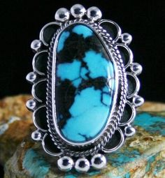 Alfred Joe Artist, Godber Burnham Turquoise Ring #AlfredJoe This marvelous turquoise is from Joe's private collection. It is Godber Burnham mined several years ago. The natural stone is deep sky blue with black host rock matrix. It is set in a hand made bezel surrounded with a floral design. The split shank features twist and smooth wire to add further beauty to the ring. Ring Size: 9