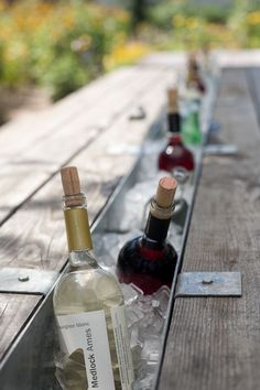 Love this!!! Remove the middle plank of a picnic table. Insert with a trough, and fill with ice for chilled bottles. Genius!