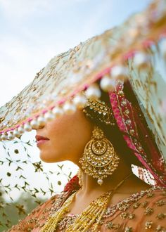 This shot! The pretty bride peeking through her ghoonghat *swoon* Don't miss these earrings - crazy pretty chaandbala alert! <3 #IndianWedding #IndianJewellery | curated by #WittyVows - The ultimate guide for the Indian Bride | www.wittyvows.com