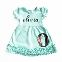 Girl's monogram mint empire waist short sleeve dress. Features your name of choice across the chest and soft floral monogram initial in the lower corner of the dress. This custom girl's dress is the p