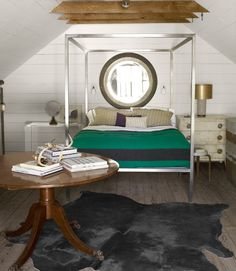In the upstairs guest bedroom of this carriage house, an Ikea cowhide rug adds luxury without overdoing it. A modern metal four-poster coexists with an English Regency table. The owner scoured area antiques stores and flea markets, uncovering such treasures as a late-1970s prototype of a mirror by legendary designer Karl Springer.   - CountryLiving.com