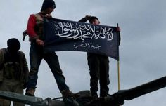 FILE - In this Friday, Jan. 11, 2013 file citizen journalism image provided by Edlib News Network, ENN, which has been authenticated based on its contents and other AP reporting, shows rebels from al-Qaida affiliated Jabhat al-Nusra waving their brigade flag on the top of a Syrian air force helicopter, at Taftanaz air base that was captured by the rebels, in Idlib province, northern Syria. Al-Qaidas branch in Iraq said it has merged with Syrias extremist Jabhat al-Nusra, a move that shows…