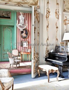 Het Huys ten Donck, Holland. An ante-room beyond the formal drawing room has walls decorated with striped wallpaper and green paint in elegant contrast to the gold and white rococo style of the music room.