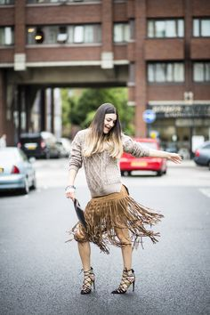 Anisa Sojka wearing brown suede Sheinside tassel skirt, khaki Sheinside cable knit loose sweater, black Rounn personalised rectangular clutch with initials 'AS', multicoloured stackable Shashi hippie bracelets and black/red/yellow/white tiled Zara strappy sandal heels. Fashion blogger streetstyle shot in London by Cristiana Malcica.