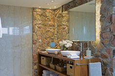 El mueble bajomesada es un diseño del Estudio, en madera, para hacerse eco del deck que rodea la bañadera. Sobre la mesada, bachas de cerámica nº 50 de Il Bel Bagno ($3.927) con grifería 'Libby' de FV ($4.809, Barugel Azulay); debajo, dos estantes sirven para guardar toallas y objetos de baño conten.  /Daniel Karp