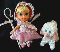 3544 Liddle Biddle Peep (1968) - Beautiful long blonde hair with bangs and three pipe curls tied up into a ponytail with a pink ribbon. Big blue eyes, a pink and white l gingham jumpsuit with lace trim, pink bustled overskirt, lace trimmed, a pink and lace bonnet and pink soft molded bow shoes. Her sheep is of white wired chenille with pink felt nose and ears and blue eyes, tending the sheep she uses her white plastic crooked staff with a pink ribbon bow, she stays awake reading her 24…