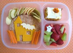 Easy Lunch boxes-Spooky Haunted House Bento! Cream cheese & jelly sandwich, orange cheddar haunted house, spooky white cheddar bat and some rickety carrot fencing. Up top are veggie chips, they don't fit in the theme, but I needed to put something there. Maybe they are storm clouds? To the right, pumpkin cake with a jack-o-lantern pick and strawberries/honeydew with a spooky little ghost.