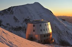 perched on top of europe's highest peak, the ovoid-shaped 'mountain hut refuge' on mont blanc. made from a wooden structure with metal cladding, the 720m2 hut can accommodate up to 120 people and is designed across four levels, the building is completely self-sufficient generating thermal energy from melted snow and electricity from solar panels  image © pascal tournaire