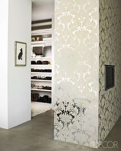 Organized walk-in closet is concealed behind a lovely damask covered wall #closet #dressing_room #wallpaper