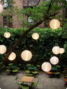 Japanese Lanterns Lighting is also about creating a mood. A series of solar-powered Japanese paper lanterns suspended from the trees gives warmth to the patio beneath.