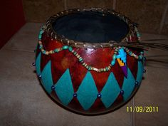 This bowl measures about 6 high and 7 1/2 in diameter. The diamond design has been carved into the gourd skin and painted turquoise. Beads embellish