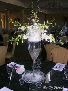 Flower Centerpieces - Great idea for New Year's Eve. Giant champaigne glass with ice/snow topped off with dendrobium orchids.