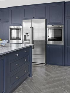 The soft, almost matte finish on the navy-blue doors and drawers in this handsome kitchen fades into the background, leaving the gleaming stainless-steel appliances to shine through.
