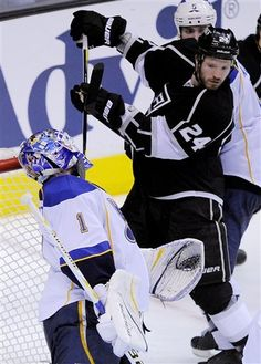 St. Louis Blues goalie Brian Elliott, left, is struck in the helmet with the stick of Los Angeles Kings center Colin Fraser during the third period in Game 4 of an NHL hockey Stanley Cup second-round playoff series, Sunday, May 6, 2012, in Los Angeles. The Kings won 3-1 and swept the series. (AP Photo/Mark J. Terrill)