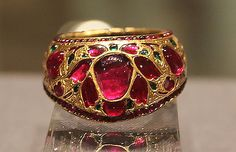 A thumb ring worn in the first half of the 17th Century, during Mughal  dynasty, and is made of gold, rubies and emeralds.