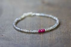 This beaded gemstone bracelet features mystic labradorite faceted rondelles, accented by plump faceted ruby rondelles. So sparkly and perfect, great for wearing on its own or stacking with other favorites. Finished with a sterling silver lobster clasp and findings.  (If youd prefer a different gemstone accent in place of the ruby, just let me know.... I have many to choose from!)  This bracelet is fairly delicate... labrdarorite rondelles measure approx 3-3.5mm apiece. Bracelet measures 7…