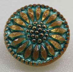 Czech 18mm glass button, daisy design in matte gold with turquoise wash from BohoBeadPeddler (Etsy) https://www.etsy.com/listing/387402176/czech-glass-button-dasiy-flower-small?ref=shop_home_active_24
