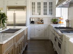 This #gourmet #kitchen has all the modern amenities including two #sinks - one double sink located on the island {#topped with marble} and one farm sink under a window. A large professional-grade range and hood take center stage. Designed by Pheobe Howard.