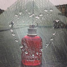 Amor Amor au musée du Louvre à Paris, un jour de pluie devant la Pyramide constituée de verre et de métal. Cœur dessiné de gouttes d'eau, mise en avant du parfum qui rime avec Amour.